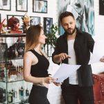 Tattoo artist showing photo portfolio to a client